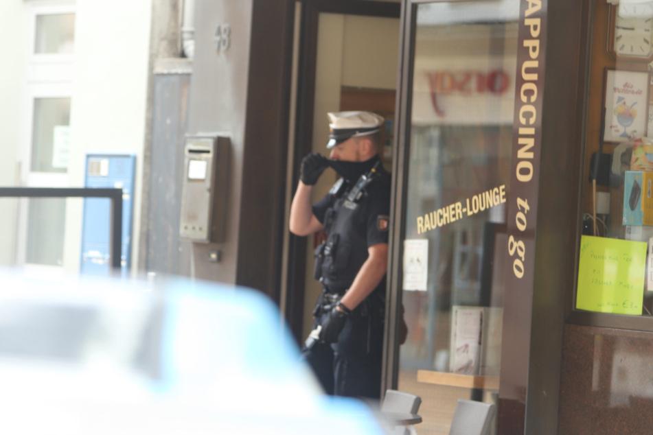 Ein Polizist steht vor dem Eiscafé in der Königstraße.