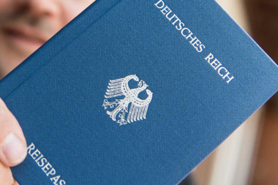 """Ein Mann hält ein Heft mit dem Aufdruck """"Deutsches Reich Reisepass"""" in der Hand."""