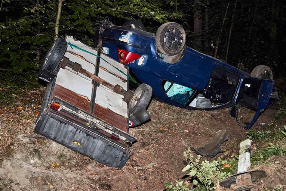 Auto und Anhänger blieben auf dem Dach im Straßengraben liegen.