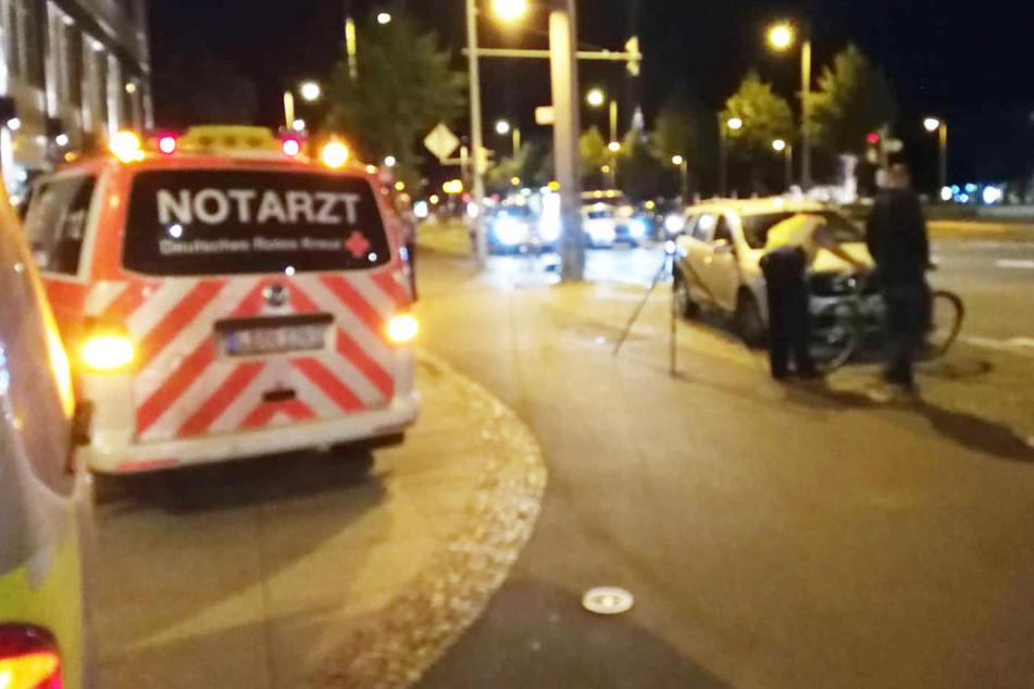 Ein Polizist begutachtet Fahrrad und Auto nach dem Unfall.