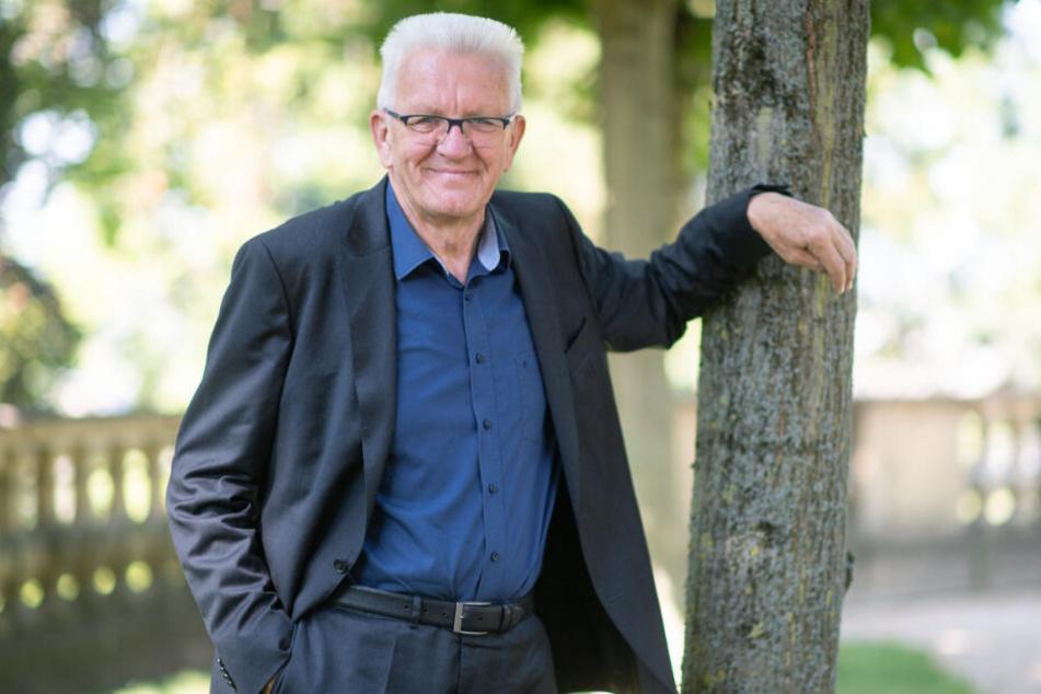 Ministerpräsident Winfried Kretschmann lehnt an einem Baum.