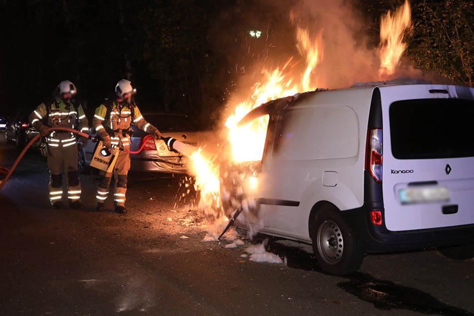 Feuerwehrleute löschen das brennende Auto.