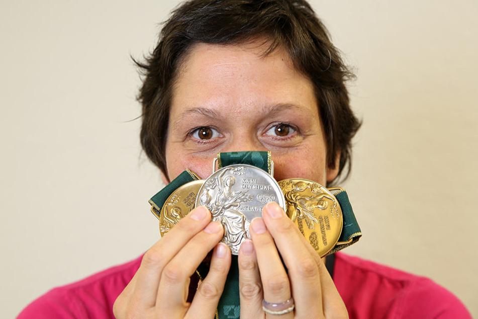 Die Ex-Schwimmerin Sandra Völker zeigt ihre Medaillen, die sie bei den Olympischen Spielen 1996 in Atlanta gewonnen hat.
