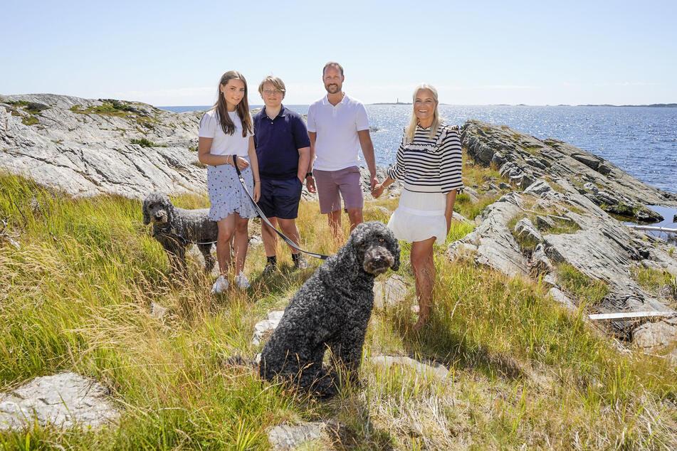 Der norwegische Kronprinz Haakon (2.v.r.), Kronprinzessin Mette-Marit (r), Prinz Sverre Magnus (2.v.l) und Prinzessin Ingrid Alexandra (l) machen Urlaub auf der Insel Dvergsøya. Die Hunde Milly Kakao (l) und Muffins Kråkebolle dürfen auf dem Familienbild nicht fehlen...