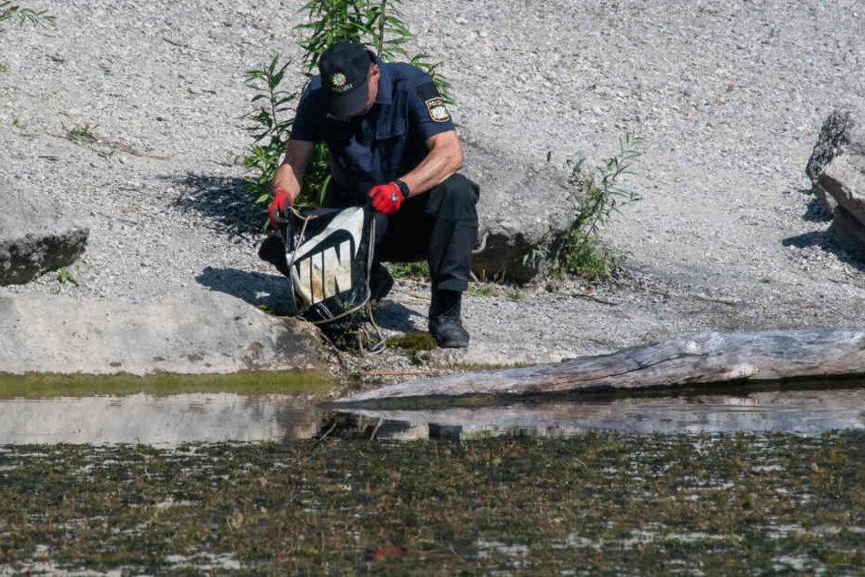 Ein Polizist durchsucht einen Turnbeutel, den Taucher im Baggersee im alten Kieswerk bei München gefunden haben.
