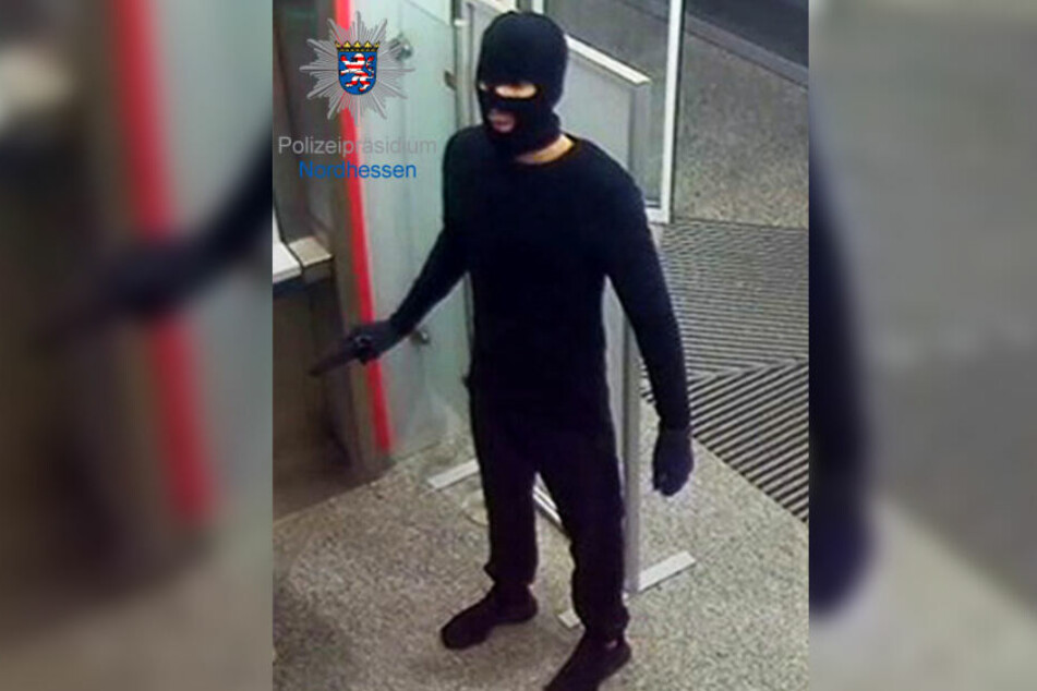 Das Foto zeigt den maskierten Räuber, der mit einer schwarzen Pistole bewaffnet war.