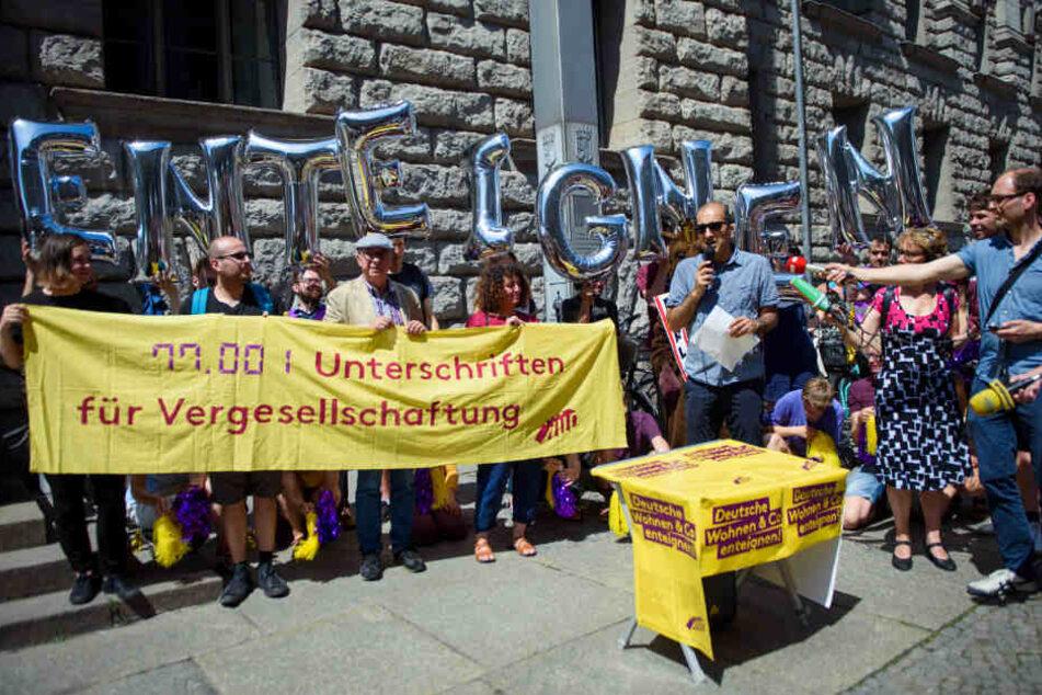 """Rouzbeh Taheri, Sprecher der Initiative Deutsche Wohnen & Co enteignen, steht vor einem Transparent """"77.001 Unterschriften für Vergesellschaftung""""."""
