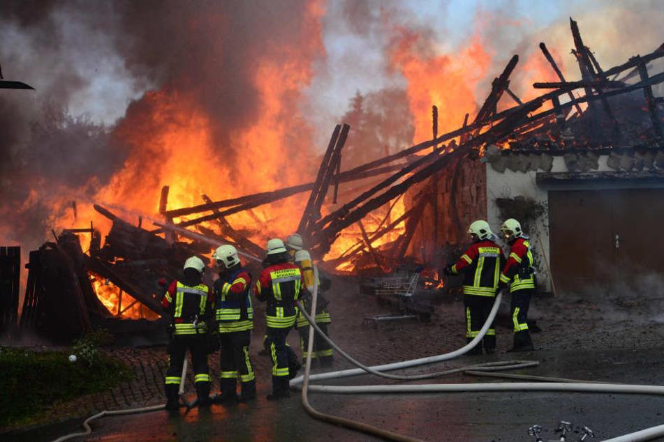 Feuerwehrmänner stehen vor dem ausgebrannten Gebäude.