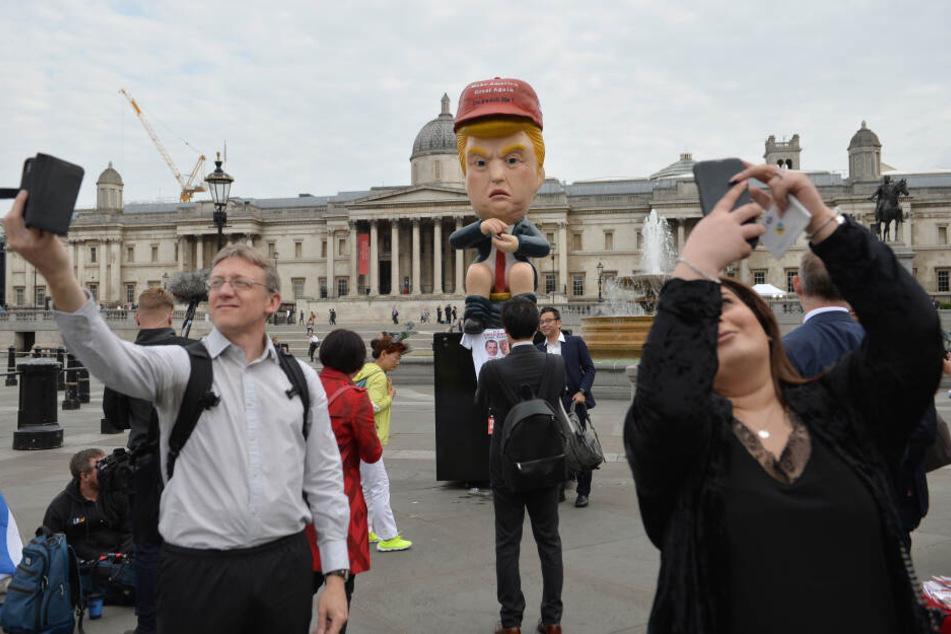 Der knapp 5 Meter große sprechende Roboter im Donald-Trump-Look sitzt auf einer Goldtoilette am Trafalgar Square.