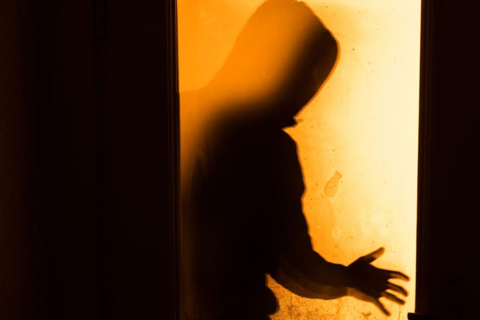 Der Schatten eines Mannes ist hinter einer Scheibe zu sehen.