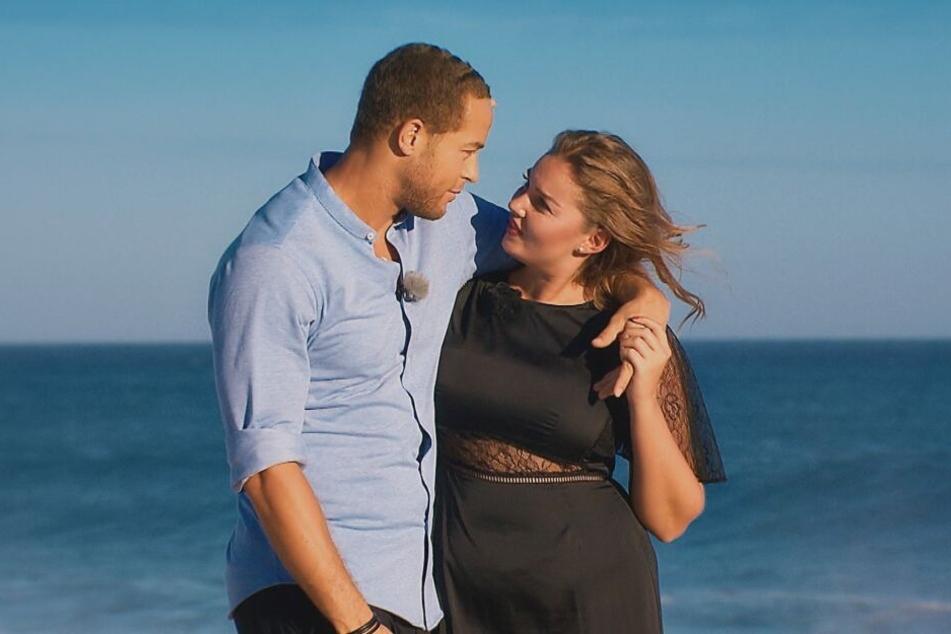 Ernestine und Andrej laufen Arm in Arm den Strand entlang.