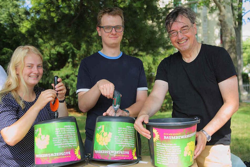 Henriette Mehn (22), Valentin Lippmann (28) und Dietrich Herrmann (56, alle Grüne) bohren je ein Loch in die Eimer.