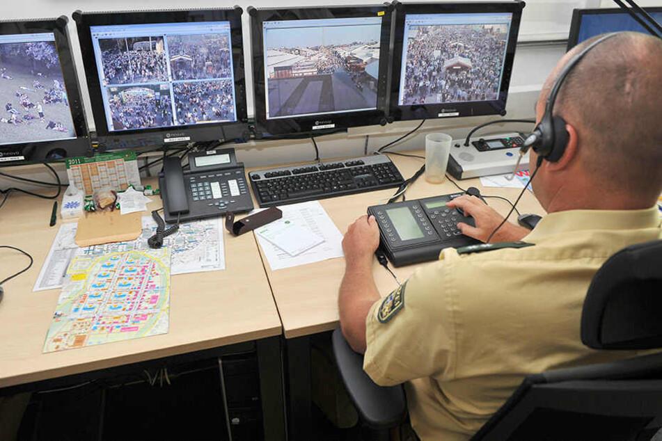 Polizisten der Wiesnwache beobachten über Bildschirme das Geschehen auf dem Oktoberfest.