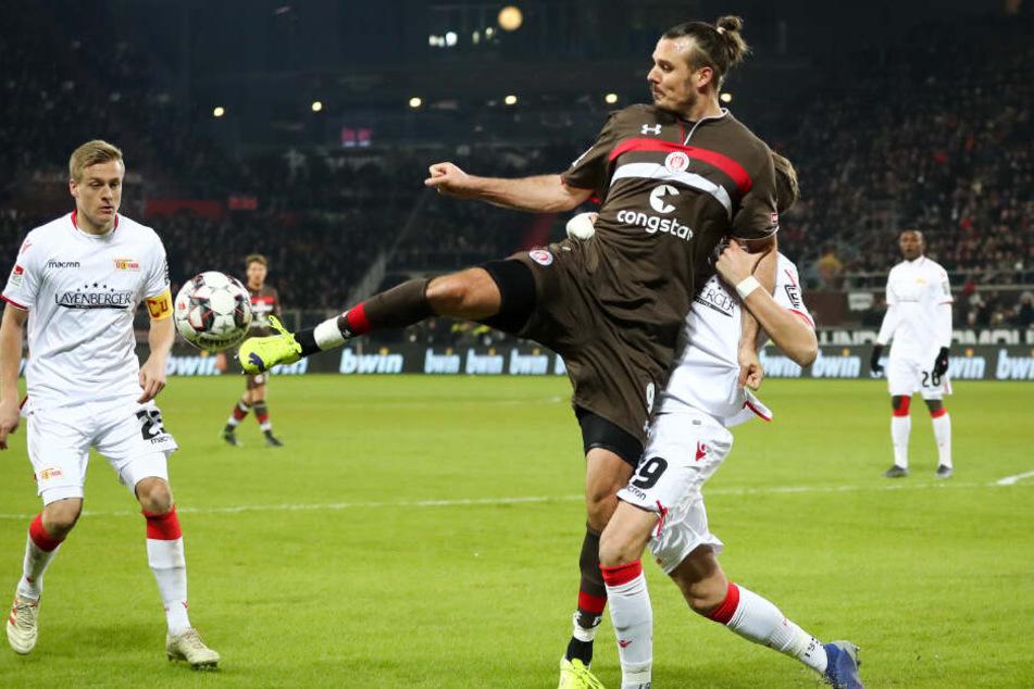 Alex Meier schirmt den Ball vor seinen Gegenspielern ab.
