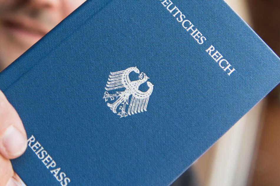 """Ein Mann hält ein Heft mit dem Aufdruck """"Deutsches Reich Reisepass"""" in der Hand (Symbolbild)."""