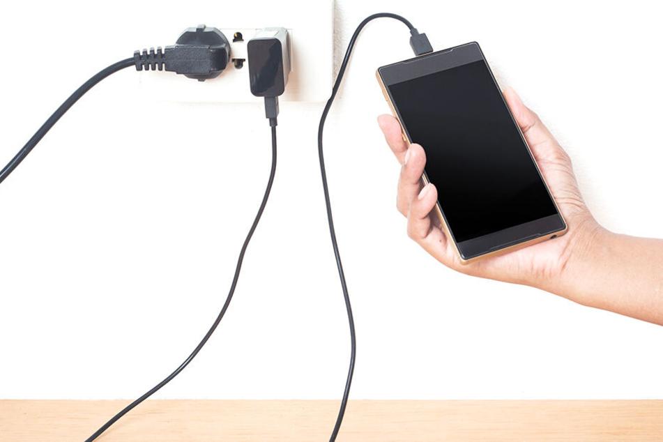 Junger Mann stirbt im Bett, während er sein Smartphone lädt
