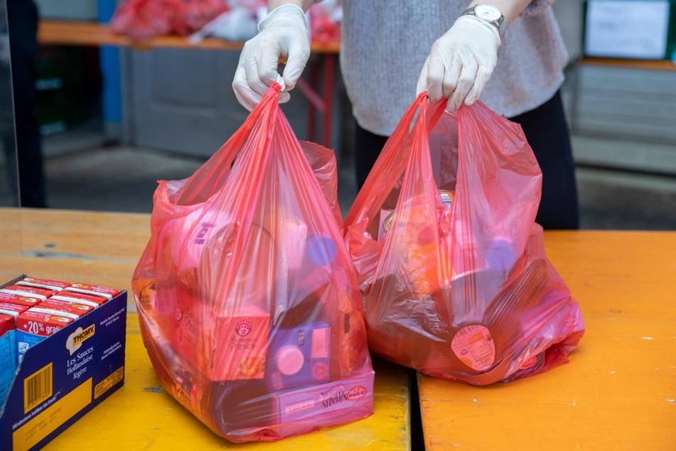 Lebensmittel in Plastiktüten werden gepackt und an Zäune gehängt.