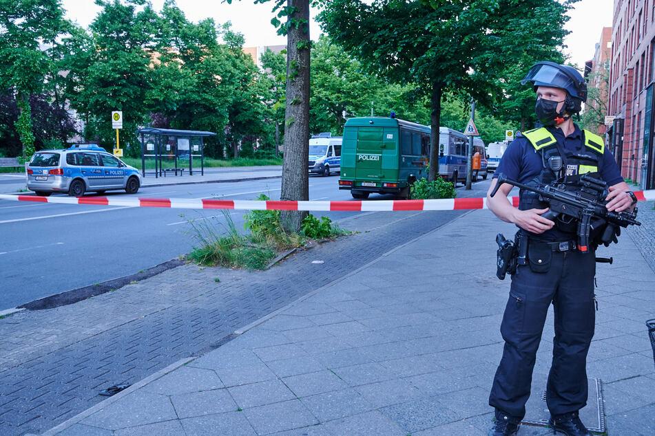 Ein schwer bewaffneter Polizist steht vor einer Absperrung in der Oranienstraße.