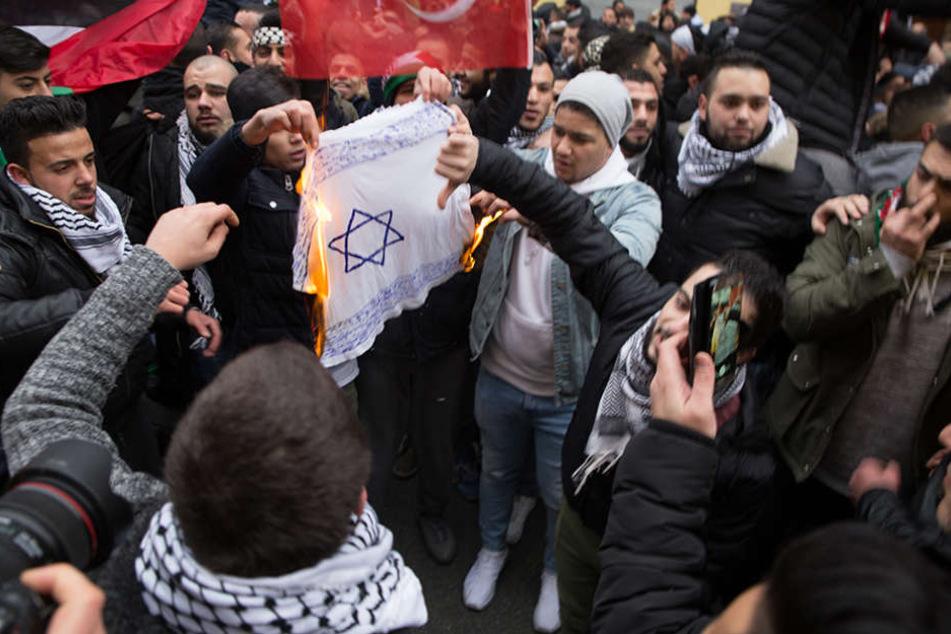 Teilnehmer einer Demonstration verbrennen eine selbstgemalte Fahne mit einem Davidstern in Berlin im Stadtteil Neukölln.