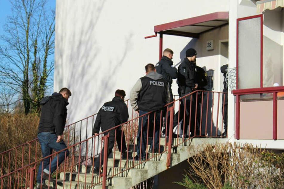 Polizisten stürmen am Morgen einen Plattenbau in Leipzig-Grünau. Eine Wohnung und der Keller werden durchsucht, danach mehrere Gegenstände beschlagnahmt.