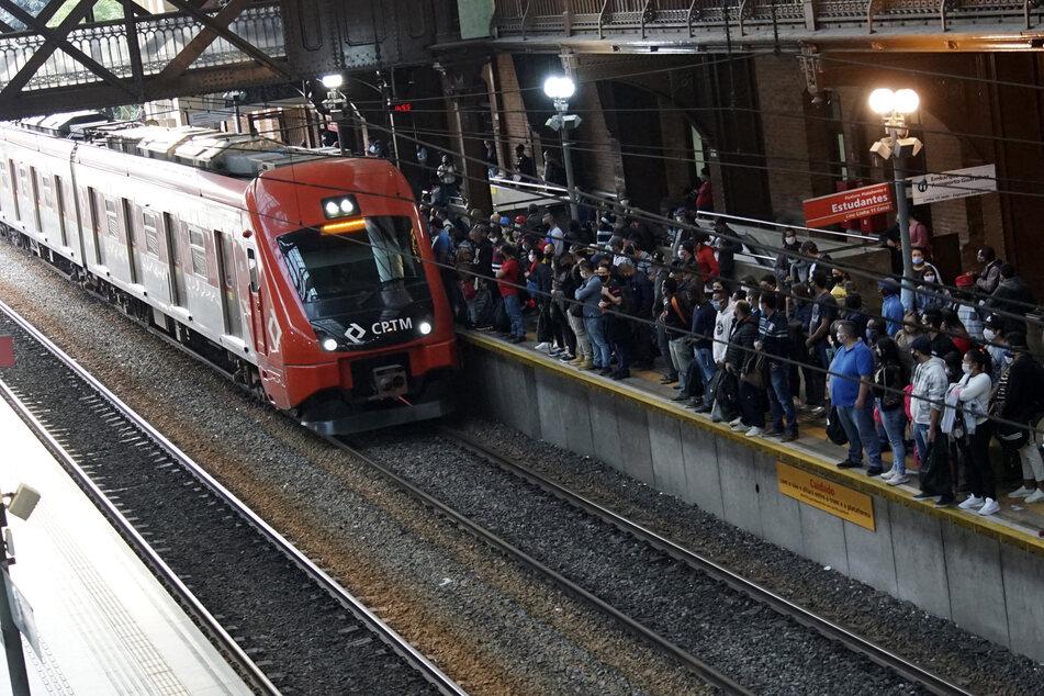 Menschen mit Mundschutzmasken stehen nah aneinander an einem Gleis inmitten der Corona-Pandemie. In der Metropole wurden Anti-Corona-Maßnahmen trotz der alarmierenden Zahlen gelockert.