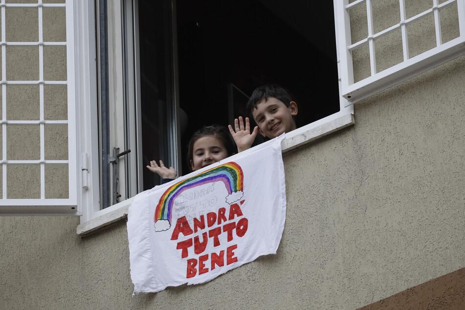 """Ein Banner mit der Aufschrift """"Alles wird gut»´"""" hängt aus einem Fenster, während Francesco und Greta Innominati herausschauen und winken."""