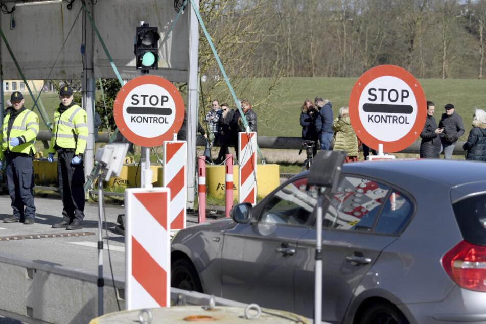 Polizisten kontrollieren am deutsch-dänischen Grenzübergang in Richtung Norden fahrende Fahrzeuge. (Archivbild)