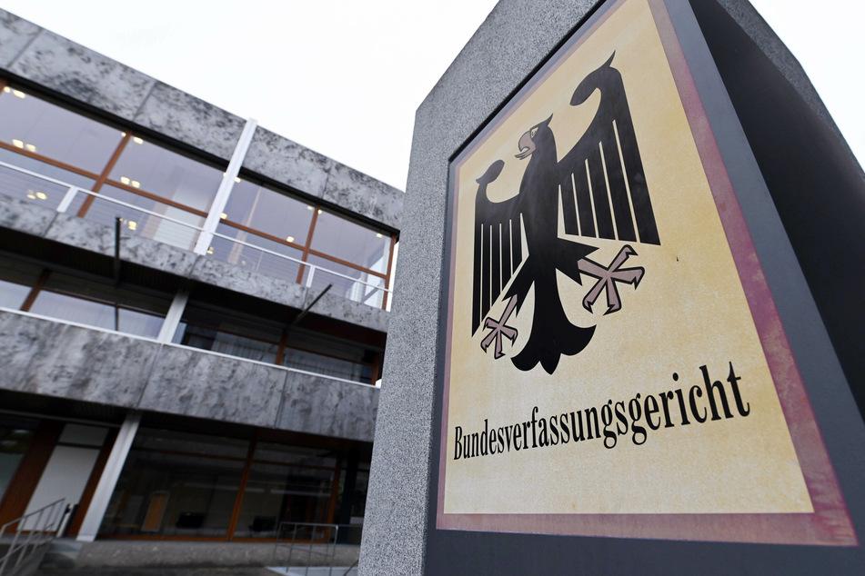 """Das Bundesverfassungsgericht mit einem Hinweisschild mit Bundesadler und dem Schriftzug """"Bundesverfassungsgericht""""."""