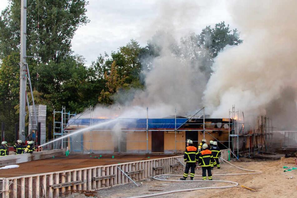 Feuerwehrleute löschen mit Wasser den brennenden Rohbau.