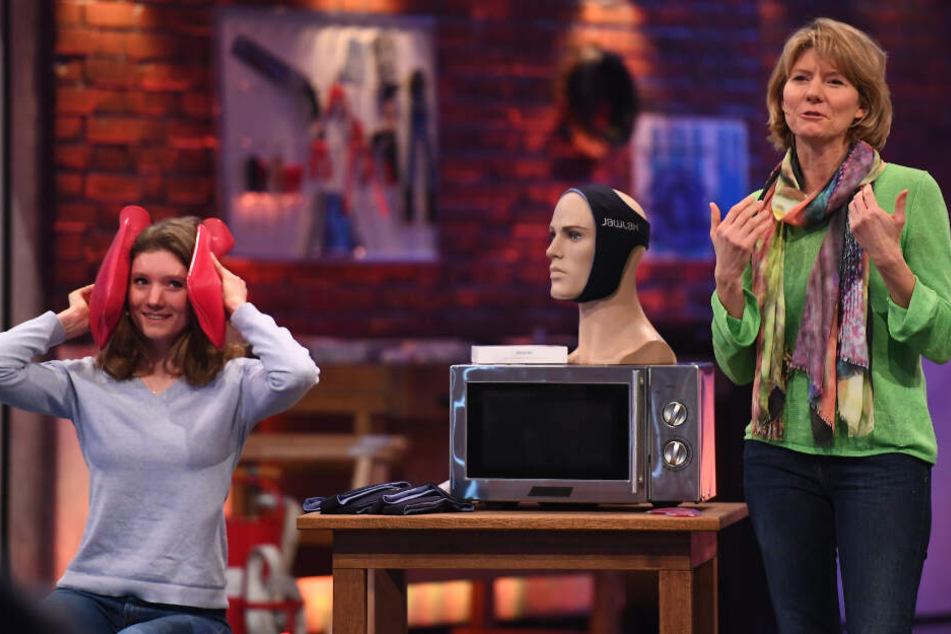 Annika (links) demonstriert eine Therapie mit Wärmflaschen - der JawLax soll das einfacher machen.
