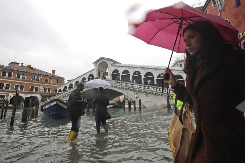 Passanten gehen in der Nähe der Rialto-Brücke durch das Hochwasser. Die Flut erreichte um 10:35 Uhr einen Höchststand von 127 cm, während für den späteren Dienstagabend ein noch höheres Niveau von 140 cm prognostiziert wurde.