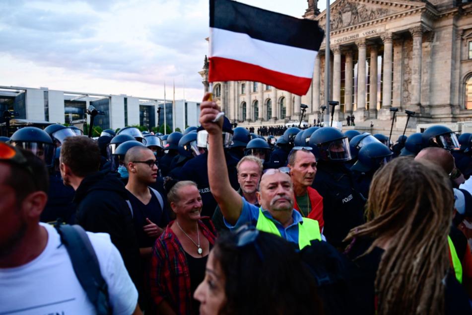 Teilnehmer einer Kundgebung gegen die Corona-Maßnahmen stehen vor dem Reichstag.