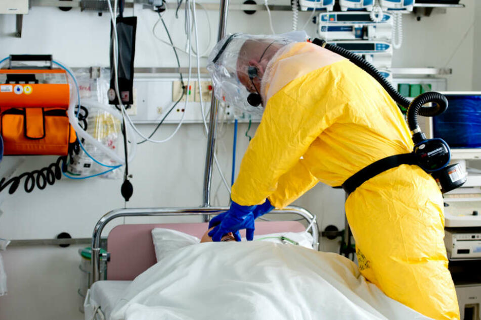 Ein Mann in Schutzausrüstung demonstriert bei einem Pressetermin die Versorgung eines Patienten auf der Sonderisolierstation im Klinikum Schwabing in München. (Symbolbild)