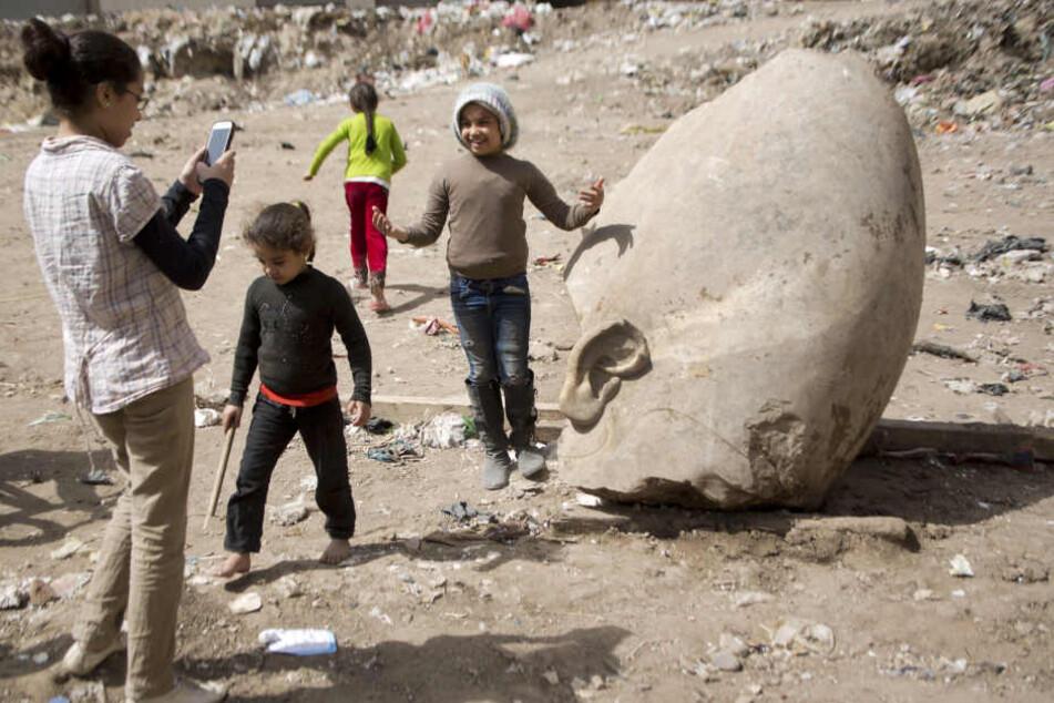 Der Koloss aus der Nachbarschaft: Kinder aus dem Wohngebiet in Kairo posieren  vor der entdeckten Statue
