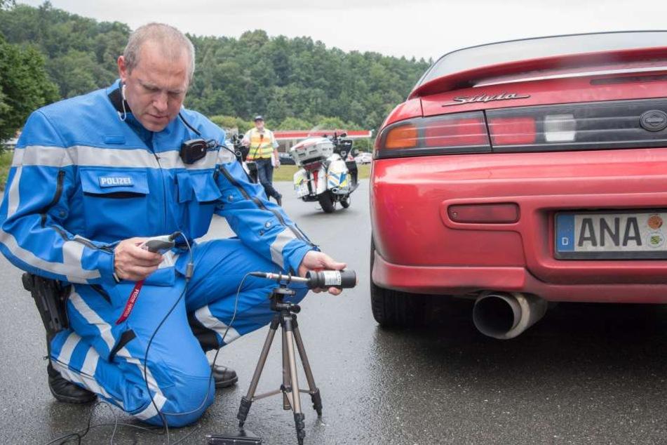 """Für den Fahrer des roten """"Nissan"""" war's das: Polizeihauptkommissar Ringo Schneider (45) stellte am Auspuff 104 Dezibel Lautstärke fest - Bußgeld, Weiterfahrt verboten."""
