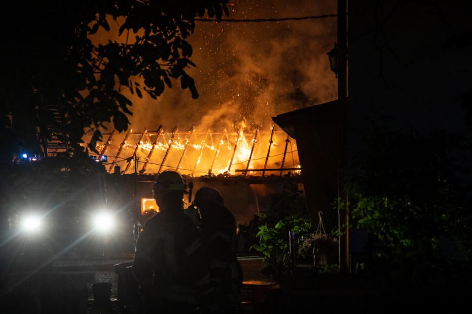 Feuerwehrleute stehen vor dem brennenden Gebäude.