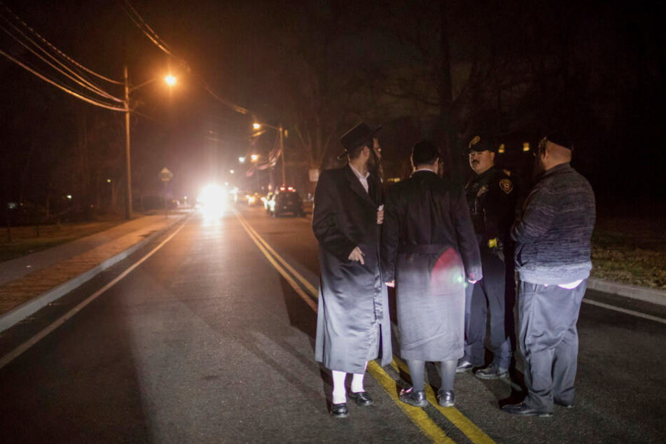Orthodoxe Juden sprechen nach einem Messerangriff mit einem Polizeibeamten (2.v.r) in der Forshay Road.