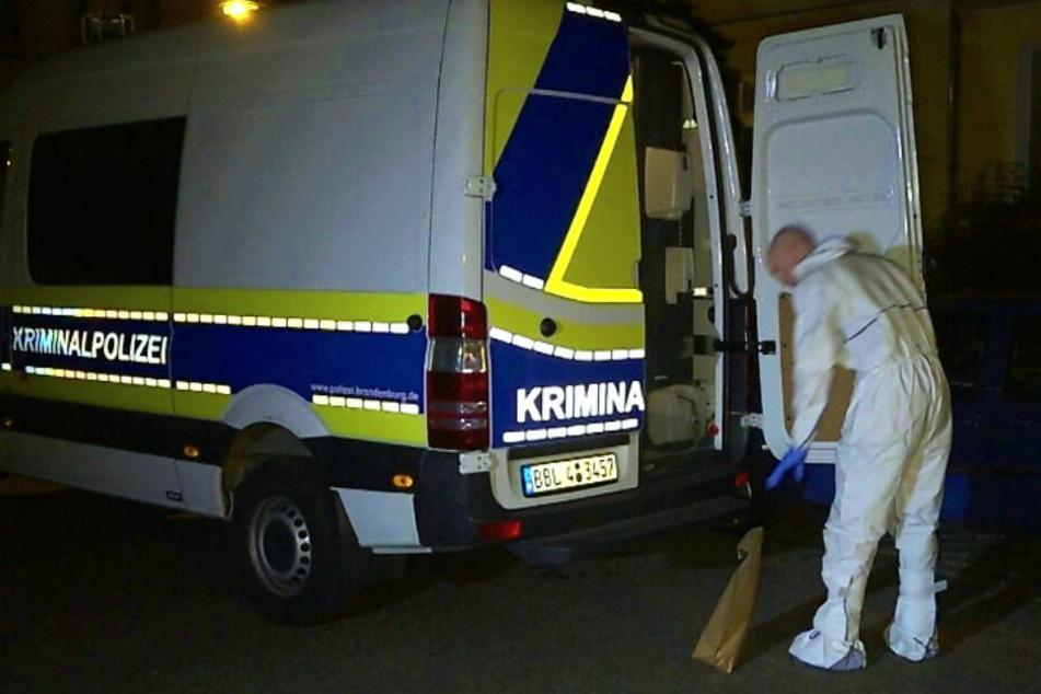 Kriminaltechniker kommen in Schutzanzügen zur Wohnung.