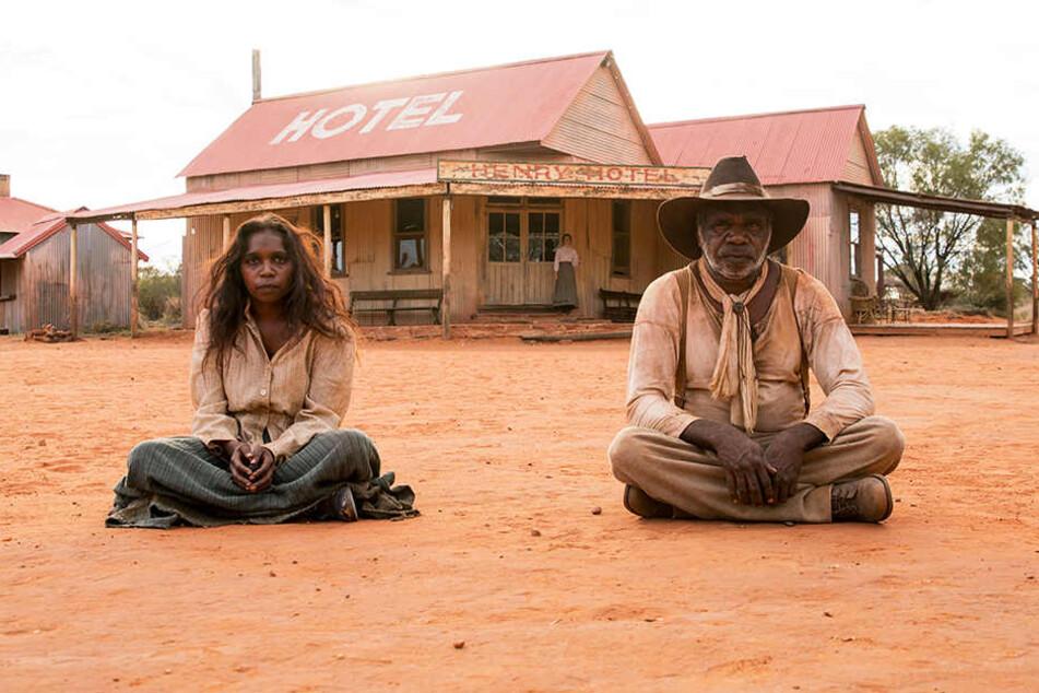 Sam Kelly (r., Hamilton Morris) und seine Frau Lizzie (l., Natassia Gorey Furber) warten in der Kleinstadt im australischen Outback vor der einzigen Kneipe.