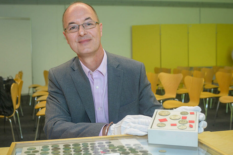 Ingo Kraft vom Landesamt für Archäologie zeigt einen Teil der Münzen.