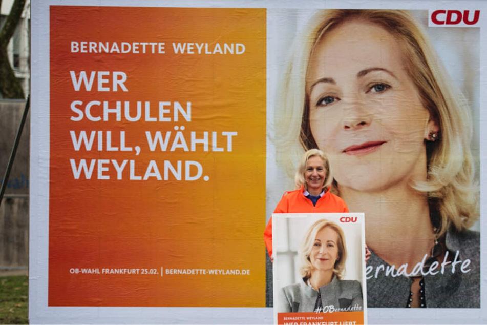 """Die CDU-Kandidatin Bernadette Weyland steht vor ihrem Plakat zum Thema """"Schulen""""."""