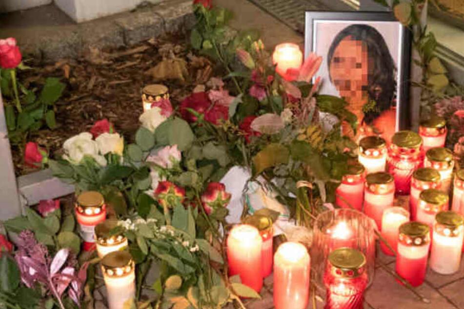 Trauernde haben Blumen und Kerzen vor das Wohnhaus der Getöteten gelegt.