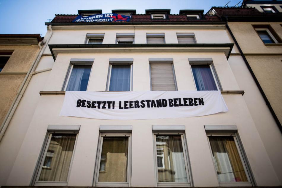 """Ein Banner mit der Aufschrift """"Besetzt! Leerstand beleben"""" hängt an einem besetzten Haus im Stuttgarter Stadtteil Heslach."""