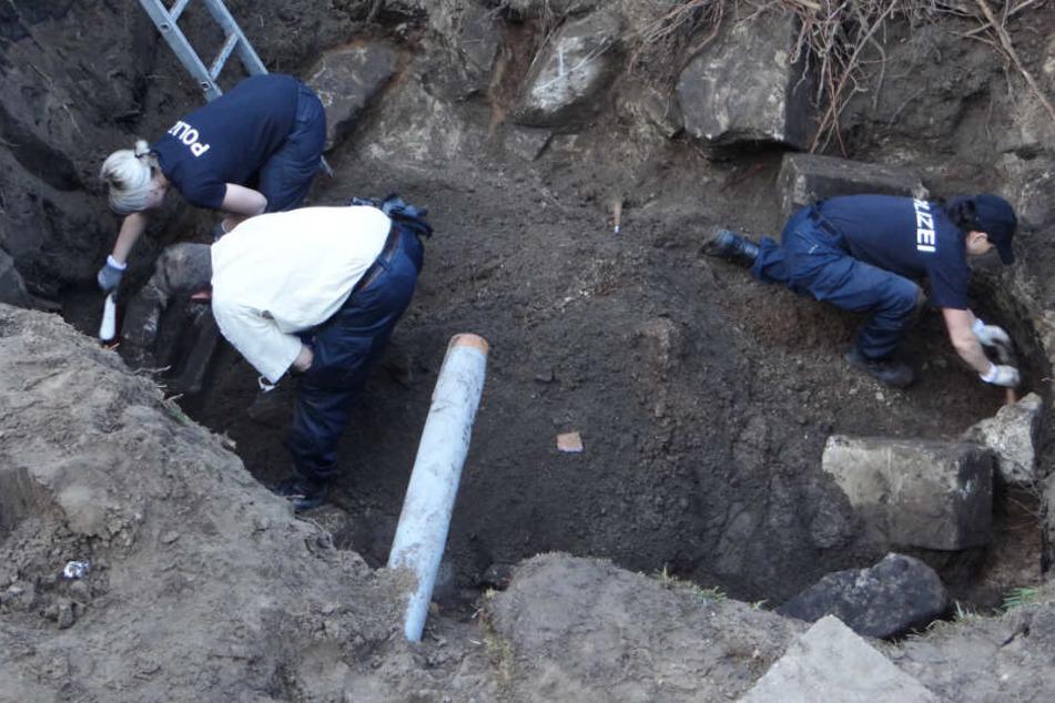 Polizisten graben nach Beweismitteln auf dem ehemaligen Grundstück des mutmaßlichen Täters.