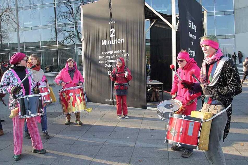 Studenten trommeln vor ihrem Klima-Denkmal für Öko-Strom an der Uni.