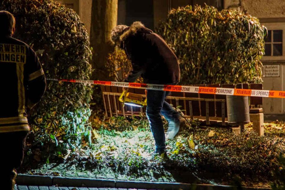 Ermittler untersuchen den Tatort, nachdem ein Mann von einem Auto aus auf offener Straße erschossen worden ist.