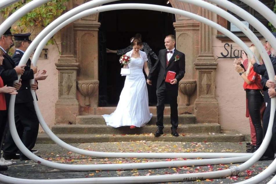 Das ist doch nicht etwa... Doch! Das Brautpaar schritt vor dem Grimmaer Standesamt durch einen meterlang aufgestellten Feuerwehrschlauch.