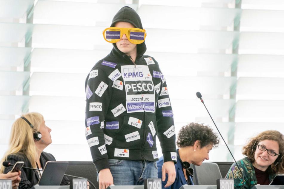 Nico Semsrott überrascht das Europaparlament: Auf seinem Pullover sind Aufkleber von Firmen, die auf die Berateraffäre von Ursula von der Leyen anspielen.