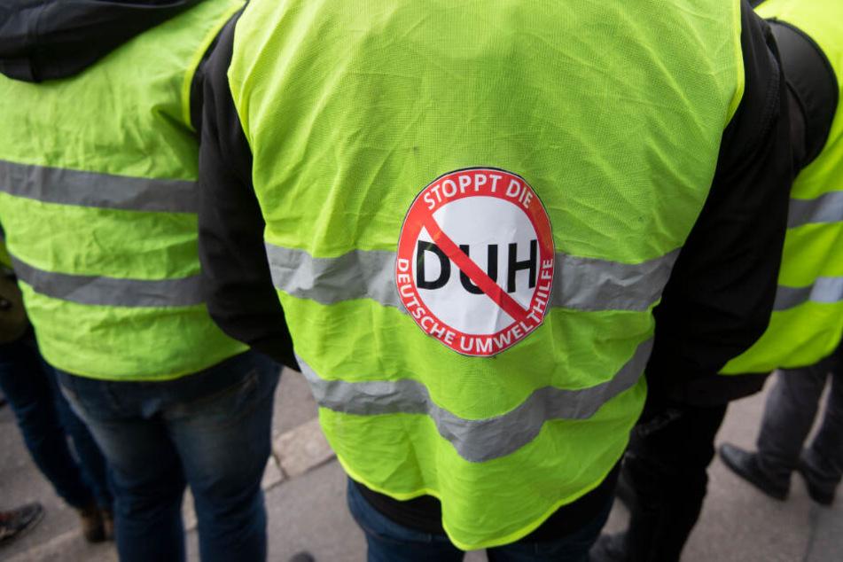 """An seiner gelben Weste hat ein Demonstrant einen Aufkleber mit """"Stoppt die Deutsche Umwelthilfe"""" kleben."""