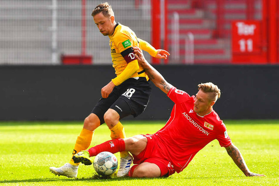 Dynamo-Kapitän Jannik Müller (l.) wird von Union-Angreifer Sebastian Polter attackiert.